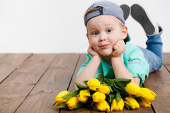 Smiling boy holding a bouquet of yellow tulips in hands sitting on wooden floor. Portrait of smiling boy with a bouquet of yellow tulips flowers in her hands Stock Photo
