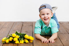 Smiling boy holding a bouquet of yellow tulips in hands sitting on wooden floor Royalty Free Stock Image