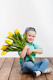 Smiling boy holding a bouquet of yellow tulips in hands sitting on wooden floor Stock Photos