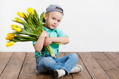 Smiling boy holding a bouquet of yellow tulips in hands sitting on wooden floor. Portrait of smiling boy with a bouquet of yellow tulips flowers in her hands Stock Image
