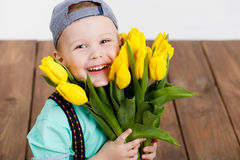 Smiling boy holding a bouquet of yellow tulips in hands sitting on wooden floor Stock Image