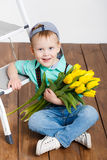 Smiling boy holding a bouquet of yellow tulips in hands sitting on wooden floor. Portrait of smiling boy with a bouquet of yellow tulips flowers in her hands Stock Images