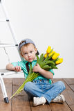 Smiling boy holding a bouquet of yellow tulips in hands sitting on wooden floor. Portrait of smiling boy with a bouquet of yellow tulips flowers in her hands Royalty Free Stock Photo