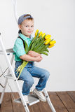 Smiling boy holding a bouquet of yellow tulips in hands sitting on wooden floor. Portrait of smiling boy with a bouquet of yellow tulips flowers in her hands Royalty Free Stock Image