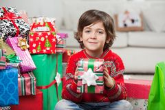 Smiling Boy Holding Christmas Gift At Home Royalty Free Stock Photography