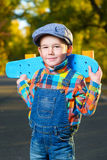 Smiling boy holding color plastic penny board Stock Photo