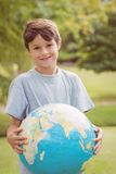 Smiling boy holding an earth globe in the park Stock Image