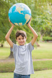 Smiling boy holding an earth globe in the park Stock Photos