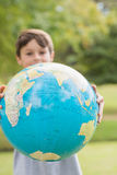 Smiling boy holding an earth globe in the park Royalty Free Stock Photos