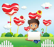 A smiling boy holding an empty signage at the candyland Stock Images