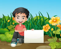 A smiling boy holding an empty signage in the garden Stock Images