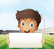 A smiling boy holding an empty signage at the soccer field Royalty Free Stock Photography