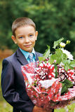 Smiling boy holding flowers Stock Photos