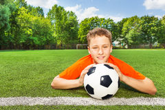 Smiling boy holding football with both arms Royalty Free Stock Photography