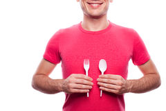 Smiling boy holding fork and spoon. Smiling handsome guy holding plastic fork and spoon near his stomach over white background. studio shot Royalty Free Stock Photos