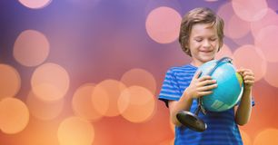 Smiling boy holding globe over bokeh Stock Photography