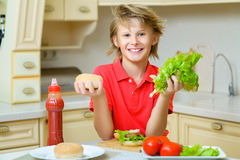 Smiling boy holding a hamburger bun and salad in Stock Photos