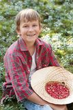 Smiling boy holding hat full of red wildberries Stock Image