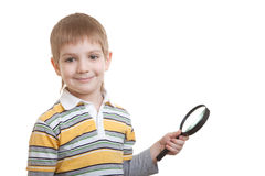 Smiling boy holding magnifying glass Stock Photo