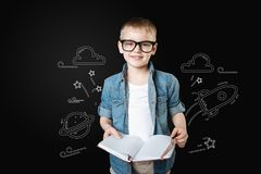Smiling boy holding a notebook and dreaming about traveling to space. Space exploration. Cheerful cute little child wearing glasses and holding a notebook while royalty free stock image