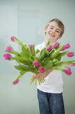 Smiling boy holding out tulip flowers against gray background Royalty Free Stock Photos