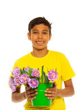 Smiling boy holding pail with pink tulips. On the white background royalty free stock photo