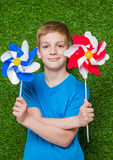 Smiling boy holding pinwheels over grass close up Royalty Free Stock Images