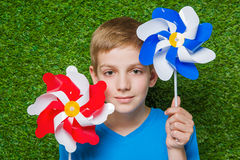 Smiling boy holding pinwheels over grass close up Stock Photo
