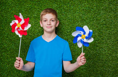 Smiling boy holding pinwheels over grass Stock Photography