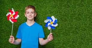 Smiling boy holding pinwheels over grass Royalty Free Stock Image