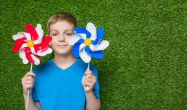 Smiling boy holding pinwheels Stock Photo