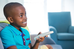 Smiling boy holding remote control on sofa at home Royalty Free Stock Photo