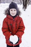 Smiling boy holding snow heart Royalty Free Stock Photography