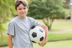 Smiling boy holding a soccer ball in the park Royalty Free Stock Image