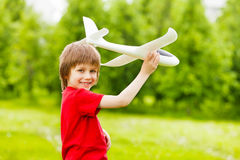Smiling boy holding white airplane toy alone Royalty Free Stock Images