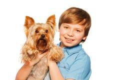 Smiling boy holding Yorkshire terrier Stock Image