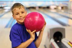 Smiling boy holds ball in bowling club Royalty Free Stock Photos