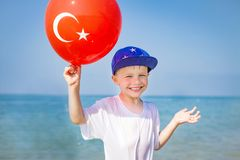 Smiling boy holds balloon with turkish flag on blue sea background on sunny summer day. Happy caucasian child on resort beach royalty free stock photos