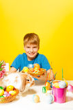Smiling boy holds plate with Eastern eggs Stock Photography