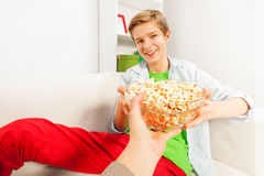 Smiling boy holds popcorn bowl from someone's hand Stock Image
