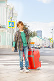 Smiling boy holds red luggage and walks on street Stock Photography