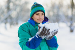 The smiling boy holds snow in hands outdoor Stock Photos