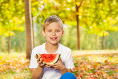Smiling boy holds watermelon sitting on the leaves Stock Images