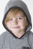 Smiling boy in a hood. Young boy wearing striped shirt and hood smiling at the camera Royalty Free Stock Photography