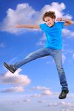 Smiling boy jumping and dancing in blue cloudy sky Stock Photos