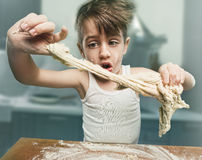 Smiling boy kneading the dough. Smiling little boy kneading the dough Stock Photo