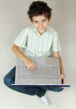 Smiling boy with laptop working on the floor Royalty Free Stock Image