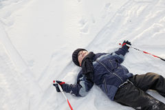 Smiling boy laying down on snow Royalty Free Stock Image