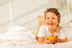 Smiling boy laying in his bed with orange juice Royalty Free Stock Photo