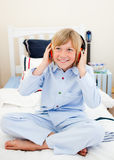 Smiling boy listening music sitting on bed Stock Image